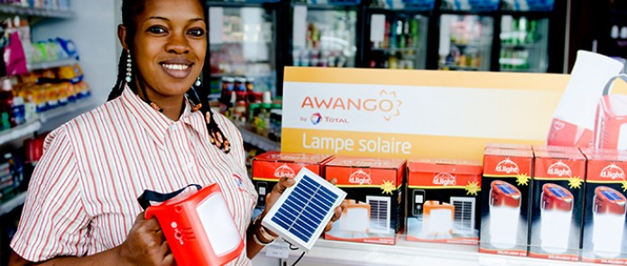 A woman sells solar lights at a petrol station in Dakar, Senegal © Andres Bifani / Lighting Africa