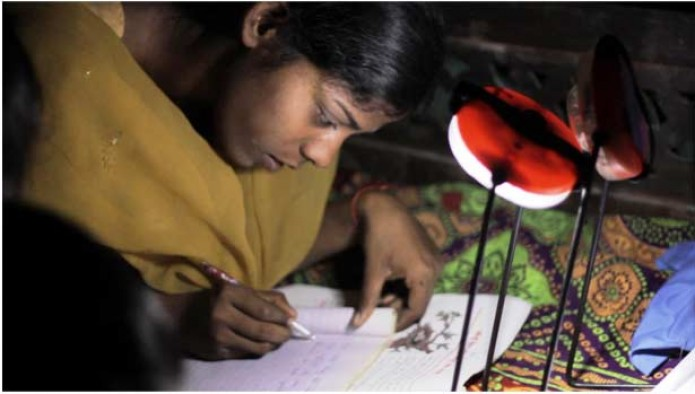 A girl in India does her homework using a modern solar-powered lamp © Lighting Asia