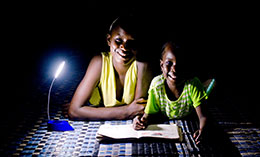Children on the outskirts of Dakar use a solar-powered reading light to do their homework © Bruno Demeocq/Lighting Africa
