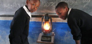 Boys using a solar lantern in their school classroom.
