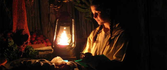 A woman in India uses a modern solar lantern to light up her kitchen as she prepares dinner © Lighting Asia