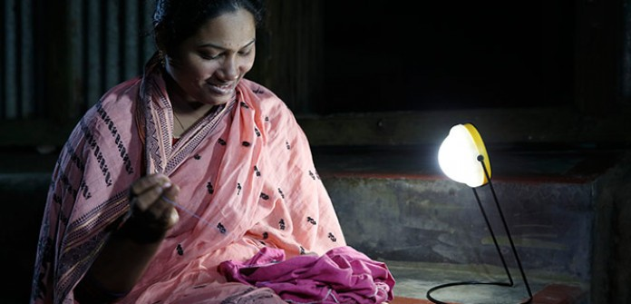 An Indian shopkeeper lights up his business with a solar LED light © Lighting Asia