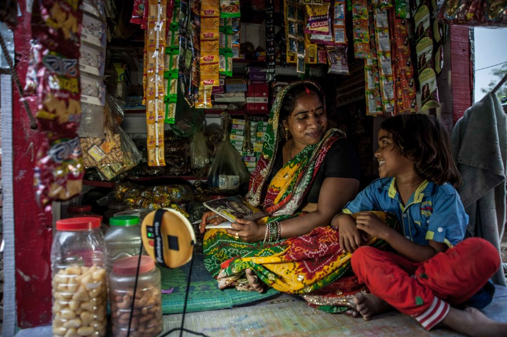 A woman and child lit with solar light in India