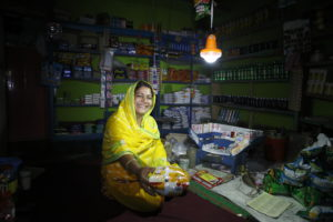 A woman works in her shop by the light of a solar powered lamp